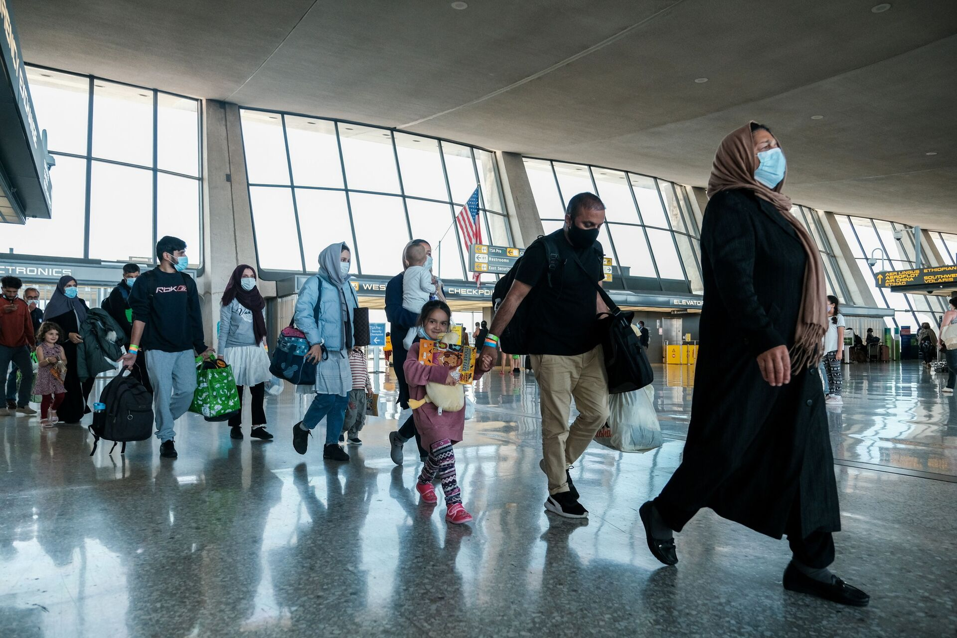 Afghan refugees walk to a bus taking them to a processing center upon arrival at Dulles International Airport in Dulles, Virginia, U.S., August 28, 2021 - Sputnik International, 1920, 15.09.2021
