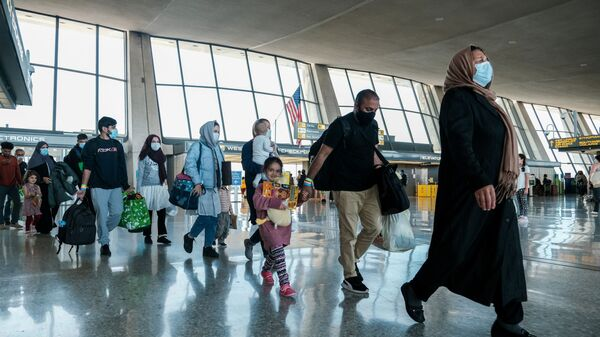 Afghan refugees walk to a bus taking them to a processing center upon arrival at Dulles International Airport in Dulles, Virginia, U.S., August 28, 2021 - Sputnik International