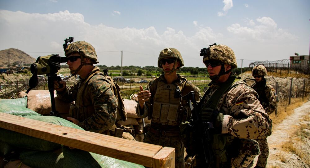 U.S. Marines and German service member watch an entry gate during an evacuation at Hamid Karzai International Airport, Kabul, Afghanistan, August 28, 2021