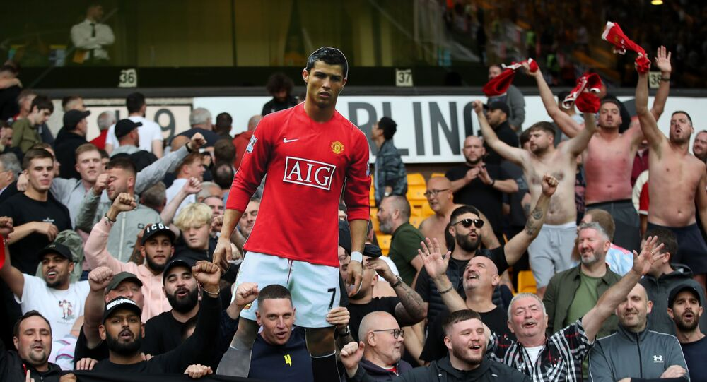 Manchester United fans celebrate with a cardboard cut out of Cristiano Ronaldo after a match.