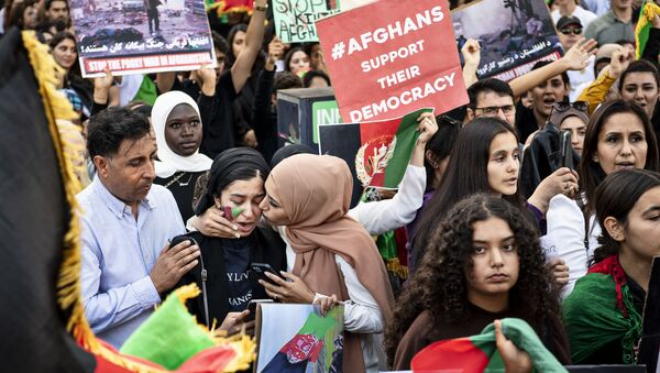Protesters wave national Afghan flags and hold banners during a rally against Pakistan's involvement in  Afghanistan following the take over of the country by the Taliban in front of the Pakistani Embassy in Copenhagen, Denmark, on August 22, 2021 - Sputnik International