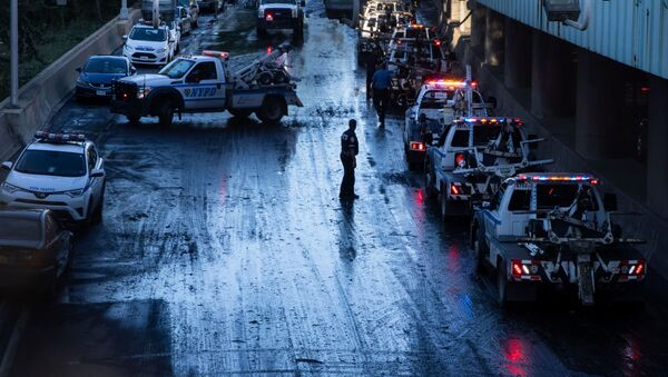 A member of the NYPD supervises tow trucks clearing cars abandoned on the Major Deegan Expressway after the remnants of Tropical Storm Ida brought drenching rain, flash floods and tornadoes to parts of the northern mid-Atlantic, in the Bronx borough of New York City, U.S - Sputnik International