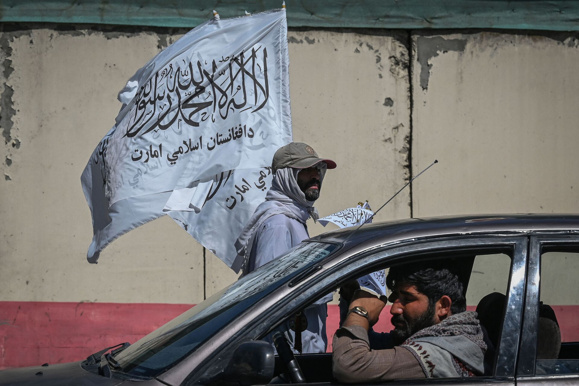 A mobile hawker carries Taliban flags as commuters make their way along a road in Kabul on September 5, 2021.  - Sputnik International, 1920, 07.09.2021
