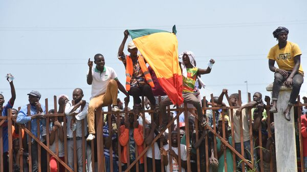 People hold up the Guinea national flag during celebrations as the Guinean Special Forces arrive at the Palace of the People in Conakry on September 6, 2021, ahead of a meeting with the Ministers of the Ex-President of Guinea, Alpha Conde.  - Sputnik International