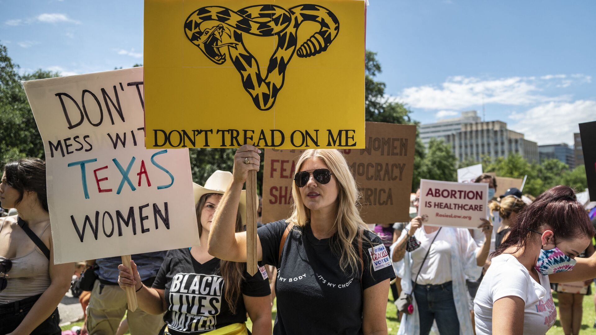 Protesters hold up signs at a protest outside the Texas state capitol on May 29, 2021 in Austin, Texas. - Sputnik International, 1920, 08.09.2021