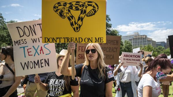 Protesters hold up signs at a protest outside the Texas state capitol on May 29, 2021 in Austin, Texas. - Sputnik International