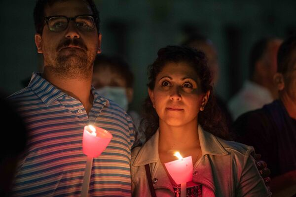 A couple holds candles as they attend a religious 9/11 commemoration ceremony at the Greek Orthodox St. Nicholas National Shrine adjacent to the 9/11 Memorial & Museum in New York City on 10 September 2021. - Sputnik International