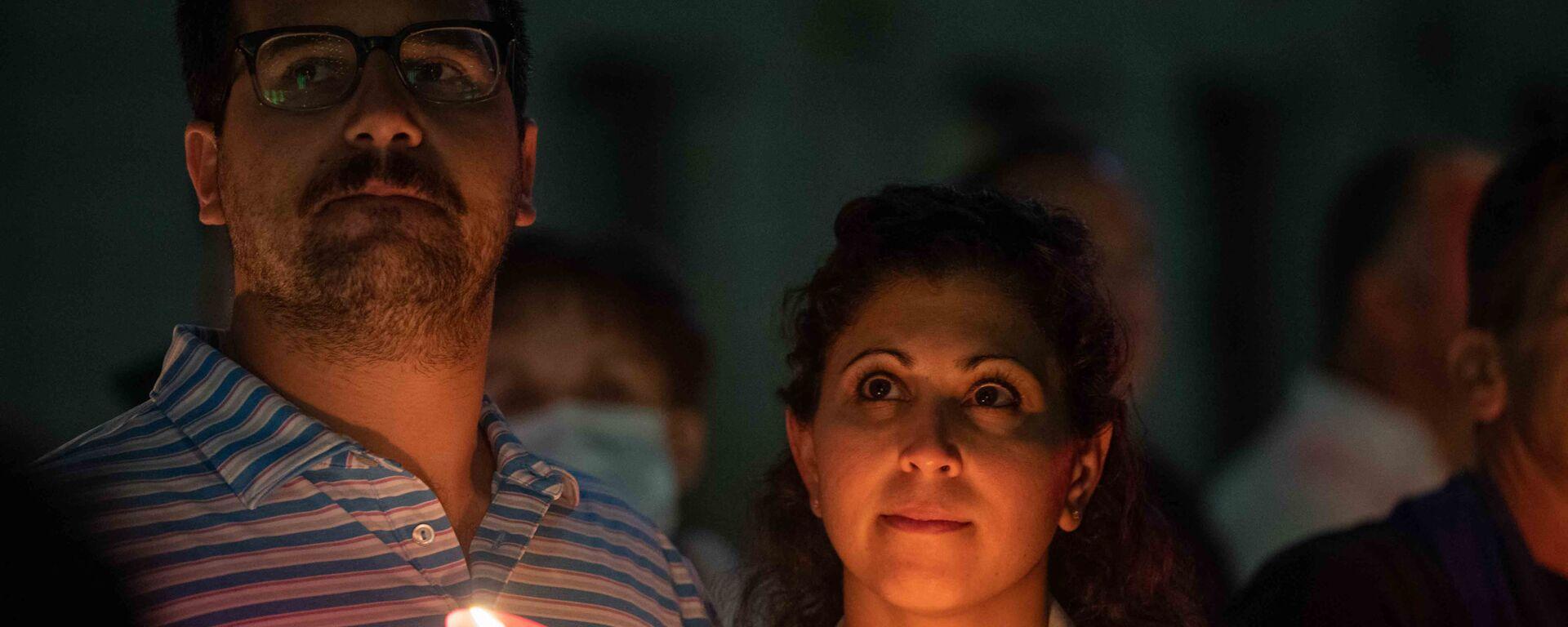 Пара держит зажженные свечи во время религиозной церемонии в память об 11 сентября в Свято-Никольском национальном храме-памятнике при Всемирном торговом центре, Нью-Йорк, США - Sputnik International, 1920, 11.09.2021