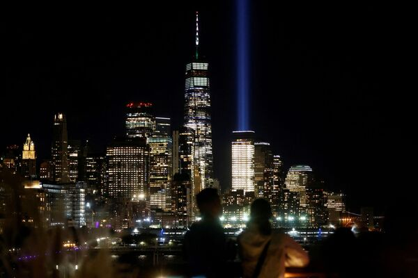 """A couple views the """"Tribute in Light"""" beams and the One World Trade Centre tower from Little Island park on the eve of the 20th anniversary of the September 11th attacks in Manhattan, New York City, US, 10 September 2021. - Sputnik International"""