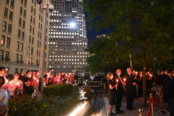 People hold candles as they attend a religious 9/11 commemoration ceremony at the Greek Orthodox St. Nicholas National Shrine adjacent to the 9/11 Memorial & Museum in New York City on 10 September 2021. - Sputnik International