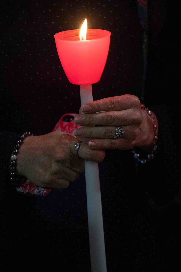 A woman holds a lit candle during a religious 9/11 commemoration ceremony at the Greek Orthodox St. Nicholas National Shrine adjacent to the 9/11 Memorial & Museum in New York City on 10 September 2021. - Sputnik International