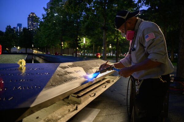 A worker cleans a display showing the names of the lives lost in the 9/11 terrorist attacks before a reflecting pool at the 9/11 memorial in New York on 10 September 2021. - Sputnik International