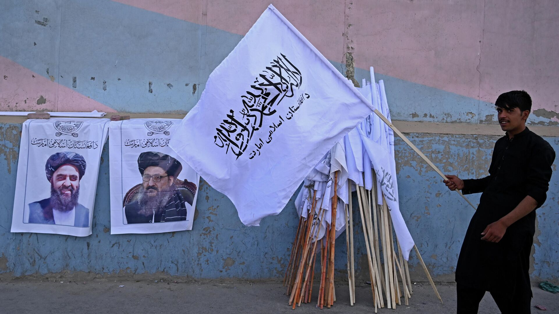 A vendor holds a Taliban flag next to the posters of Taliban leaders Mullah Abdul Ghani Baradar and Amir Khan Muttaqi (L) as he waits for customers along a street in Kabul on August 27, 2021, following the Taliban's military takeover of Afghanistan - Sputnik International, 1920, 15.09.2021