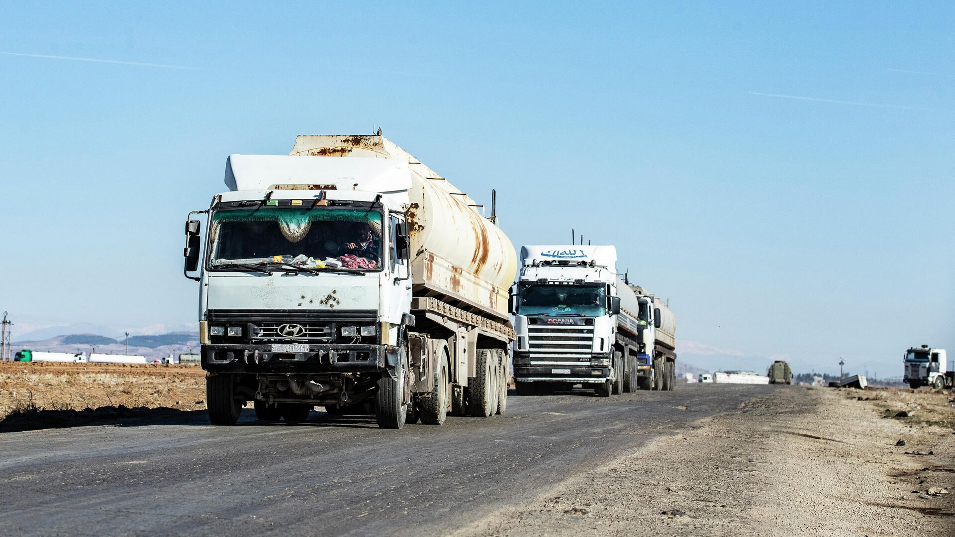 Tank trucks advance on a road at the Rumaylan (Rmeilan) oil fields in Syria's Kurdish-controlled northeastern Hasakeh province, on January 6, 2021, transporting the valuable resource to government-controlled areas - Sputnik International, 1920, 15.09.2021