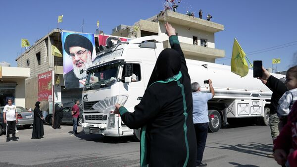 A woman throws flower petals and rice as a convoy of tanker trucks carrying Iranian fuel oil drive in al-Ain village, in northeastern Lebanon, September 16, 2021. - Sputnik International