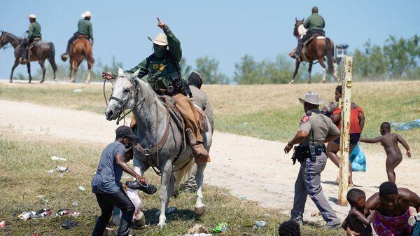 Пограничный патруль США на лошади пытается помешать гаитянскому мигранту войти в лагерь на берегу Рио-Гранде - Sputnik International