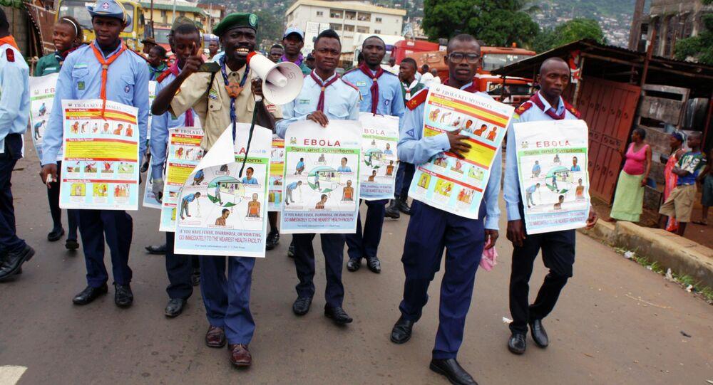 UNICEF members are holding posters detailing Ebola virus symptoms, Freetown, Sierra Leone.