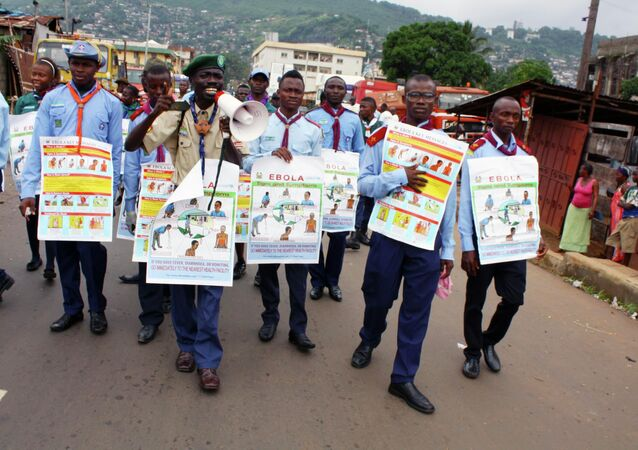 UNICEF members are holding posters detailing Ebola virus symptoms, Freetown, Sierra Leone.