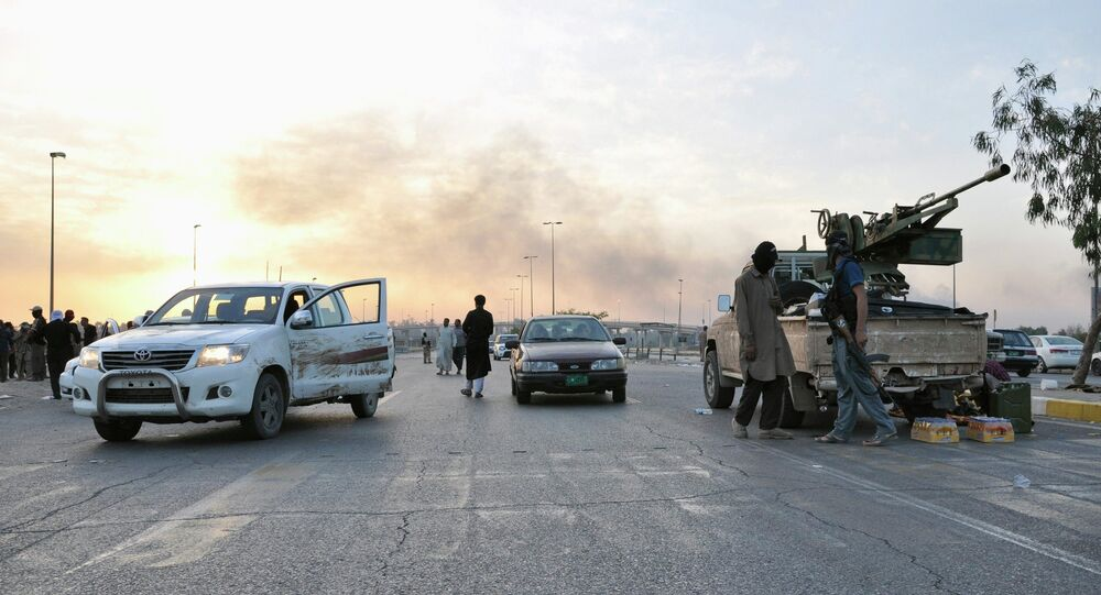 Fighters of the Islamic State of Iraq and the Levant (ISIL) stand guard at a checkpoint in the northern Iraq city of Mosul, in this June 11, 2014 file photo.