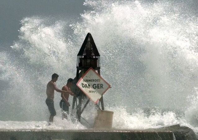 This Sept 14, 1999 file photo shows Fort Lauderdale, Fla., residents Rafael Verga, left, and Joel Vasconcelos, right, holding on as waves hit the jetty at Haulover Beach in Miami Beach, Fla., as Hurricane Floyd moves toward South Florida. Sea levels rising because of global warming, along with increased storminess as the climate changes, will expose tens of millions of people in the world's port cities to coastal flooding, says a report by the Organization for Economic Cooperation and Development.