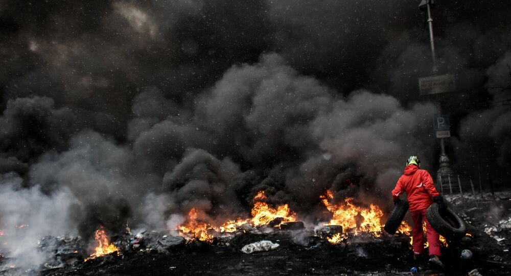 A protester adds tire to the fire in Maidan square in Kiev, Ukraine, Jan 22, 2014