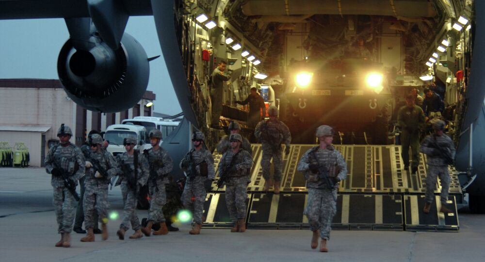 Soldiers from the 2nd Platoon, Alpha Company, 1-27 Infantry Division, assume a security perimeter as two M1126 Stryker Infantry Carrier Vehicles exit a C-17 Globemaster and drive onto the tarmac at Daegu Air Base, South Korea