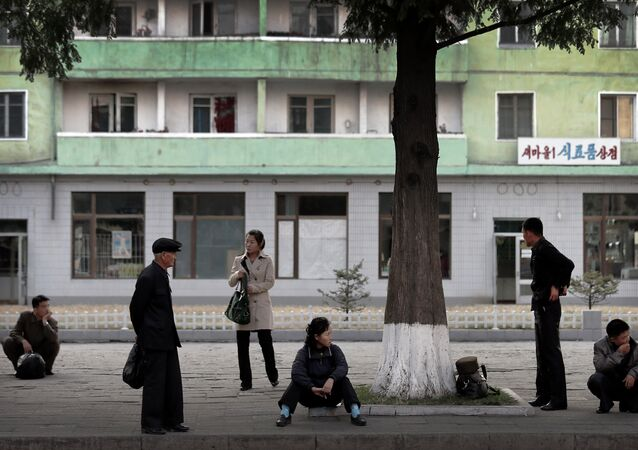 North Koreans wait at a roadside for public transport in downtown Pyongyang, North Korea