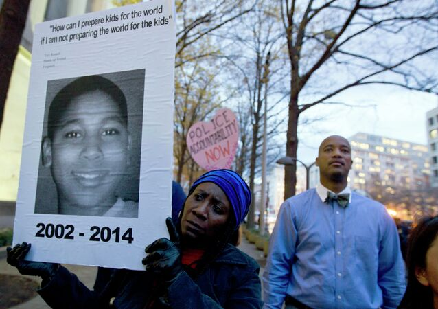 A protester holds a picture of Tamir Rice, the boy fatally shot by a rookie police officer, during a protest in response to a grand jury's decision in Ferguson to not indict police officer Darren Wilson. Protesters across the U.S. have walked off their jobs or away from classes in support of the Ferguson protesters. Rice's death has also sparked community demonstrations against police shootings.