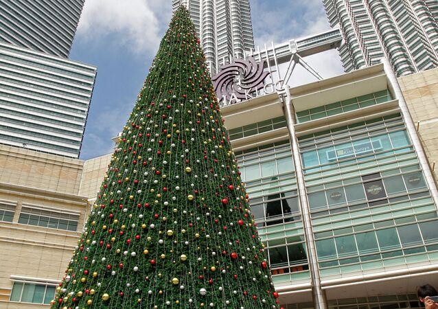 People walk around a giant Christmas tree on display against the Malaysia's landmark Petronas Twin Towers in Kuala Lumpur, Malaysia, Dec. 6, 2014
