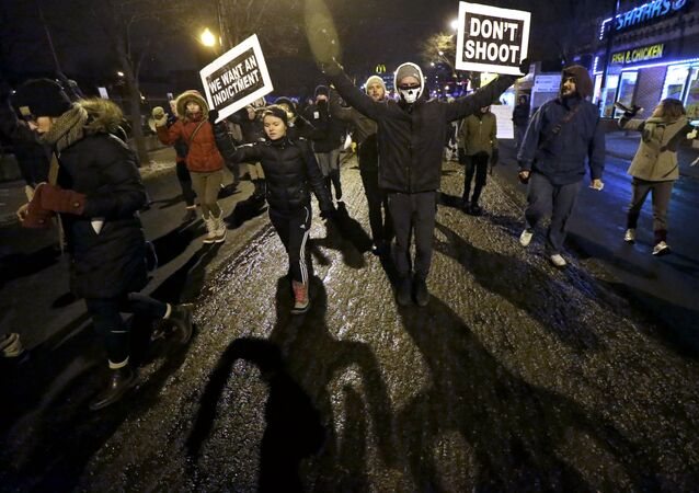 Protesters march during a rally near the Chicago Police headquarters after the announcement of the grand jury decision not to indict police officer Darren Wilson in the fatal shooting of Michael Brown, an unarmed black 18-year old, Monday, Nov. 24, 2014, in Chicago.
