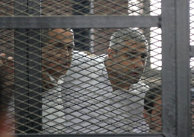 Australian journalist Peter Greste and Mohamed Fahmy stand inside court's cage
