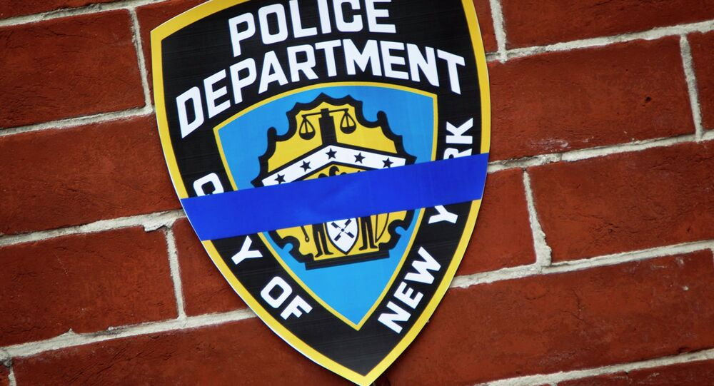 An NYPD logo is pictured on wall above makeshift memorial at the site where two police officers were shot in the head in the Brooklyn borough of New York, December 22, 2014.