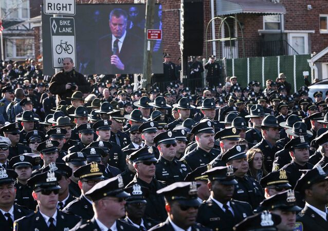 Law enforcement officers turn their backs on a live video monitor showing New York City Mayor Bill de Blasio as he speaks at the funeral of slain NYPD officer Rafael Ramos.