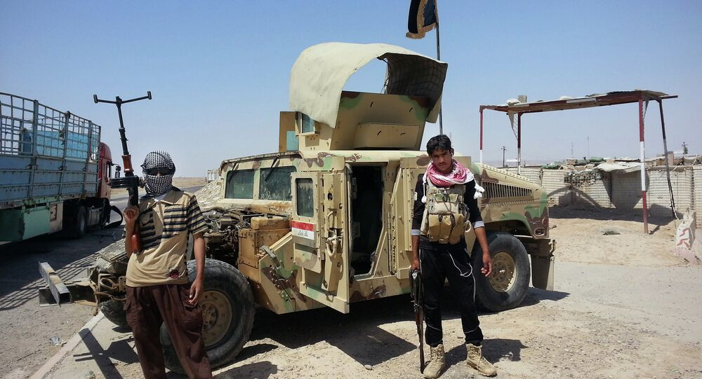 In this file photo, Daesh militants stand with a captured Iraqi army Humvee at a checkpoint outside Beiji refinery, around 155 miles north of Baghdad, Iraq.
