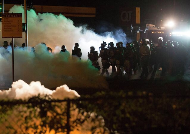 Riot police clear a street with smoke bombs while clashing with demonstrators in Ferguson, Missouri August 13, 2014.
