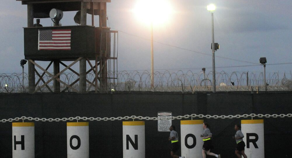 Soldiers run in front of the Honor Bound sign at Joint Task Force Guantanamo's Camp Delta.