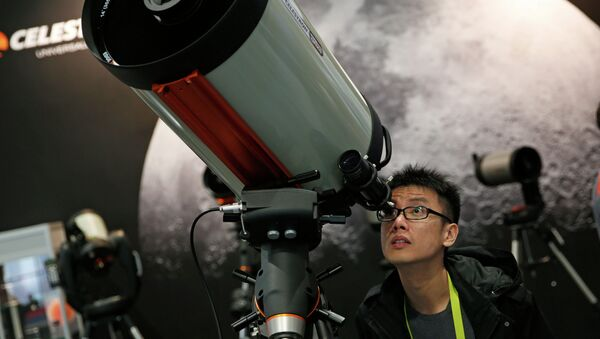 Kei Yuen Hung looks through a telescope at the Celestron booth during the International CES Friday, Jan. 9, 2015, in Las Vegas. - Sputnik International