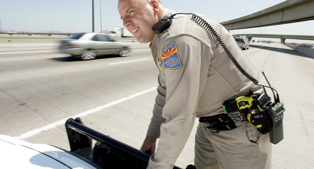 An Arizona Department of Public Safety officer adjusts the infrared license plate scanner mounted on the front bumper of his police cruiser along the I-10 in Phoenix.