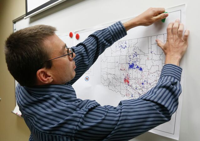 In this June 26, 2014 file photo, Austin Holland, research seismologist at the Oklahoma Geological Survey, hangs up a chart depicting earthquake activity at their offices at the University of Oklahoma in Norman, Okla. A study published Thursday, July 3, 2014 by the journal Science explains how just four wells forcing massive amounts of drilling wastewater into the ground are probably causing quakes in Oklahoma. The wells seem to have triggered more than 100 small-to-medium earthquakes in the past five years, according to a study.