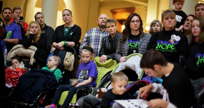This Jan. 13, 2015 file photo, shows parents of children who suffer from epilepsy. With virtually no hard proof that medical marijuana benefits sick children, and evidence that it may harm developing brains, the drug should only be used for severely ill kids who have no other treatment option, the nation's most influential pediatricians group says in a new policy.