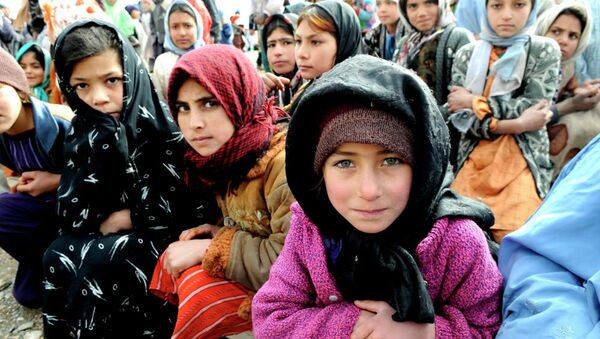 Village girls wait as humanitarians unload a shipment of food, clothing and supplies in western Afghanistan. - Sputnik International