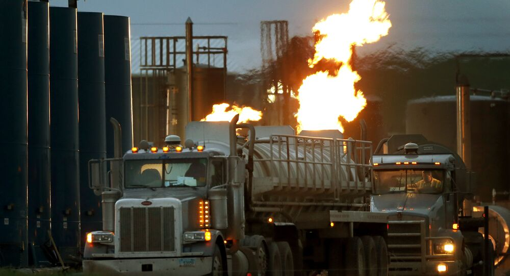 Drivers and their tanker trucks, capable of hauling water and fracking liquid line up near a natural gas burn off flame and storage tanks in Williston, N.D.