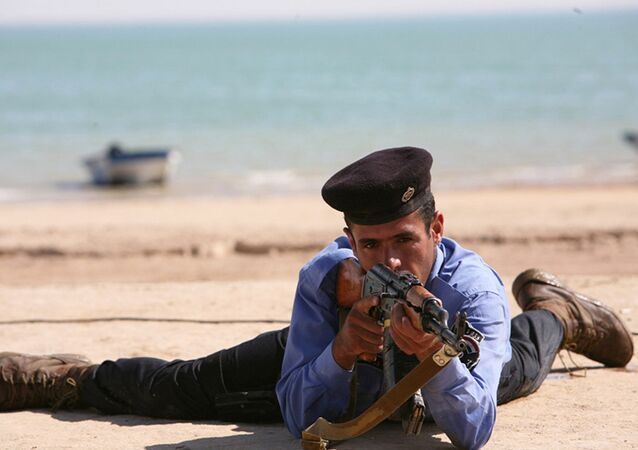 A member of Lake Habbaniyah's river police detachment participates in a beach assault demonstration for a ceremony held on the northern shore of Lake Habbaniyah, Iraq, April 21