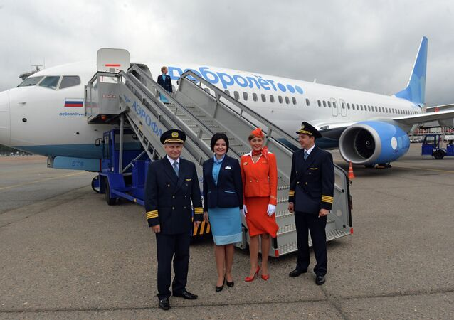 Aeroflot personnel seen beside the stairway to the Dobrolyot airliner at the Sheremetyevo airport, June 10, 2014