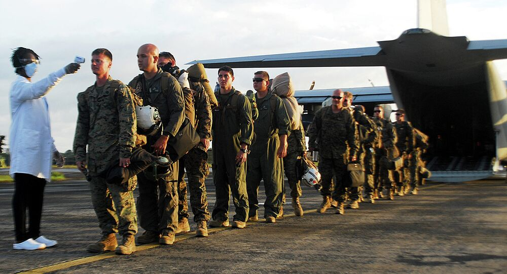 U.S. Marines stand in line to have their temperature checked as the exit the KC-130