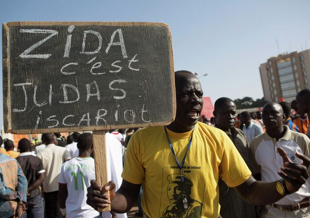 A protester carries a sign reading Zida is Judas Iscariot, referring to coup leader Lt. Col. Yacouba Isaac Zida, in Ouagadougou, capital of Burkina Faso