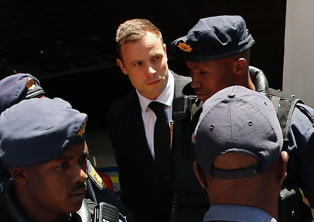 South African Olympic and Paralympic sprinter Oscar Pistorius (C) is escorted to a police van after his sentencing at the North Gauteng High Court in Pretoria October 21, 2014