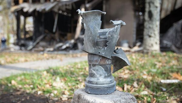 The remains of a projectile is seen in front of shops damaged by recent shellings in Donetsk, eastern Ukraine, October 21, 2014 - Sputnik International