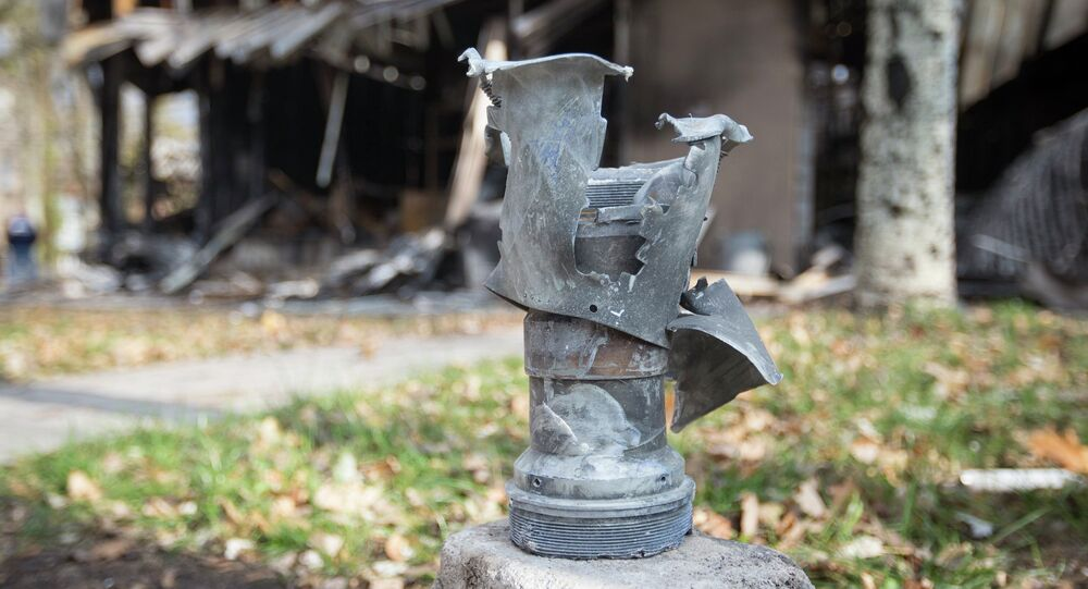 The remains of a projectile is seen in front of shops damaged by recent shellings in Donetsk, eastern Ukraine, October 21, 2014