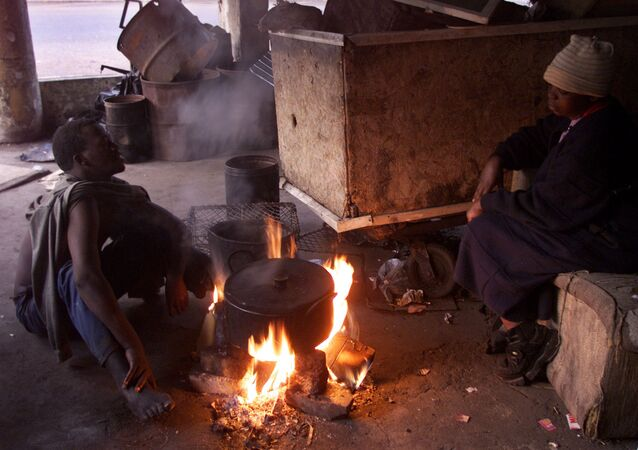 Homeless squatters sit near a fire to keep away the cold early in the morning in Johannesburg
